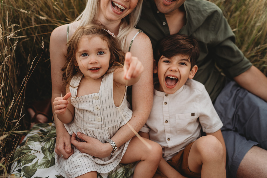 close up of two children in their parents laps , they are reaching out to the camera and laughing