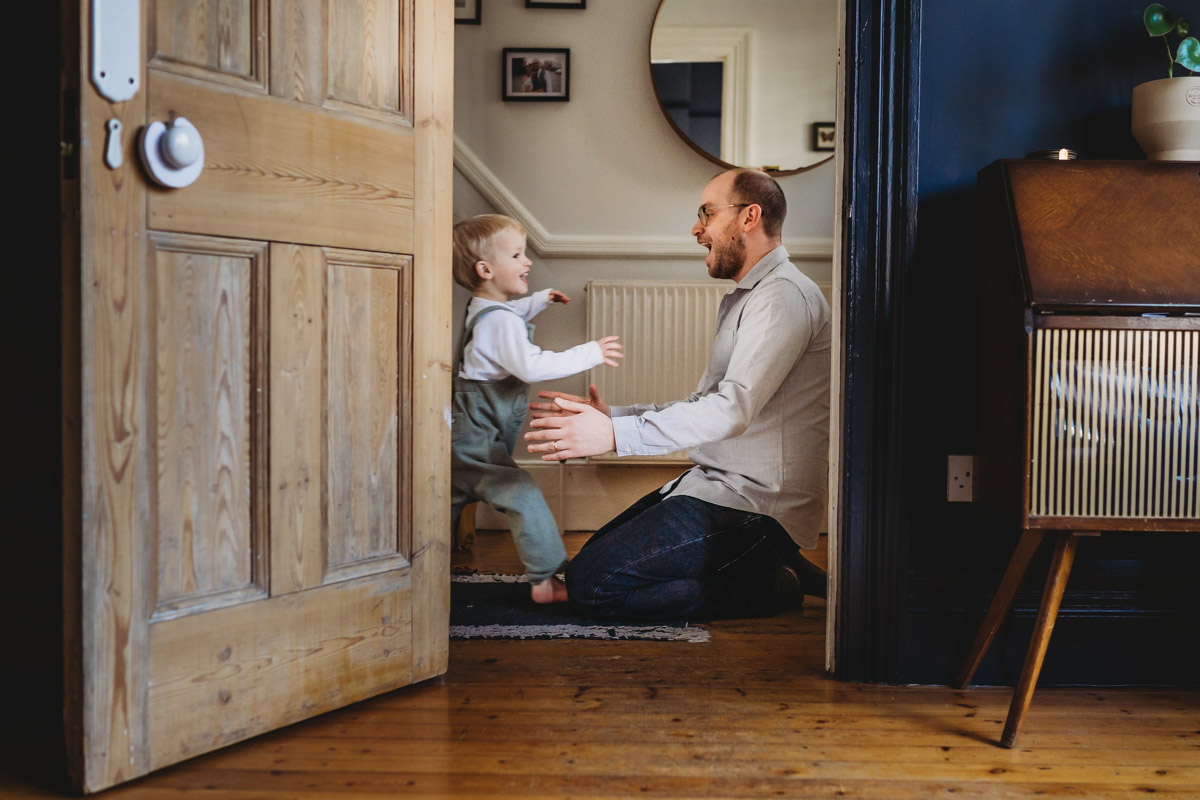 father and son at home playing being captured by Carley Aplin