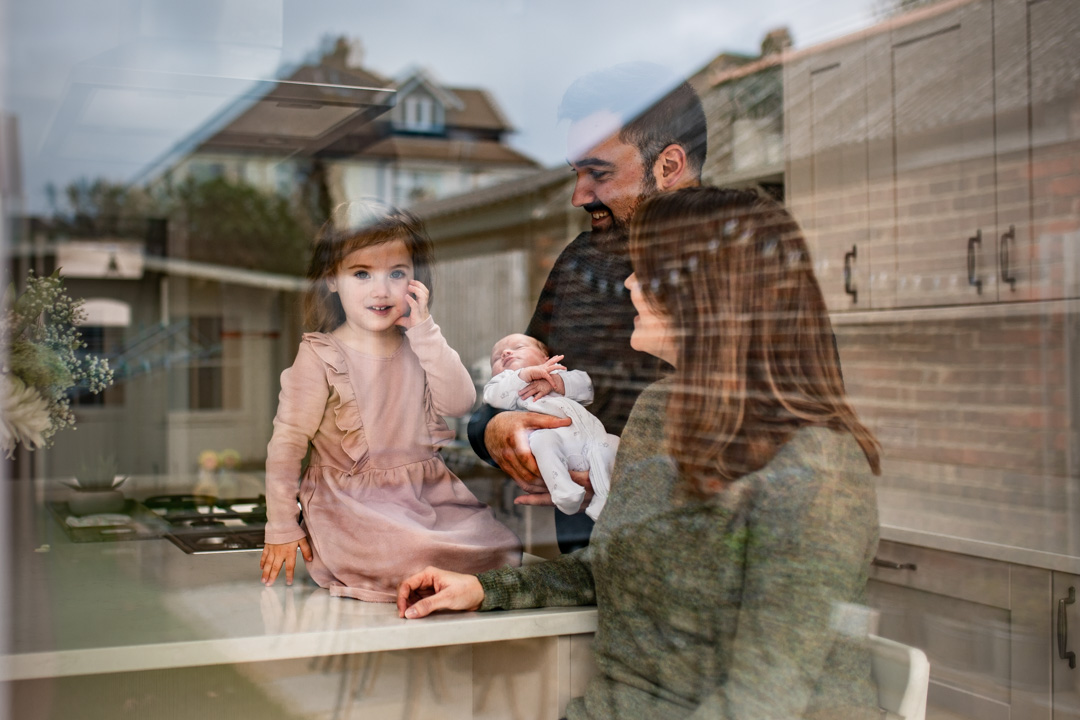 A photo of a family shop through glass you can see the reflection of the garden as the dad holds his newborn baby and his daughter sits on the worktop mum sits on a stall She is wearing a green jumper
