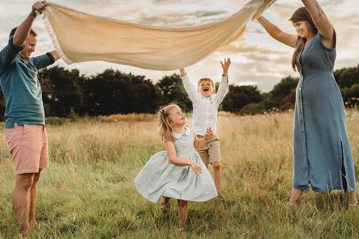 family having fun under blanket