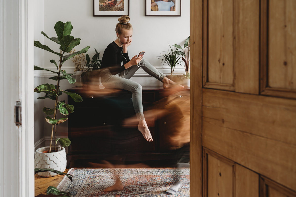 teenager sitting on her phone with a slow shutter blur of two small children running by