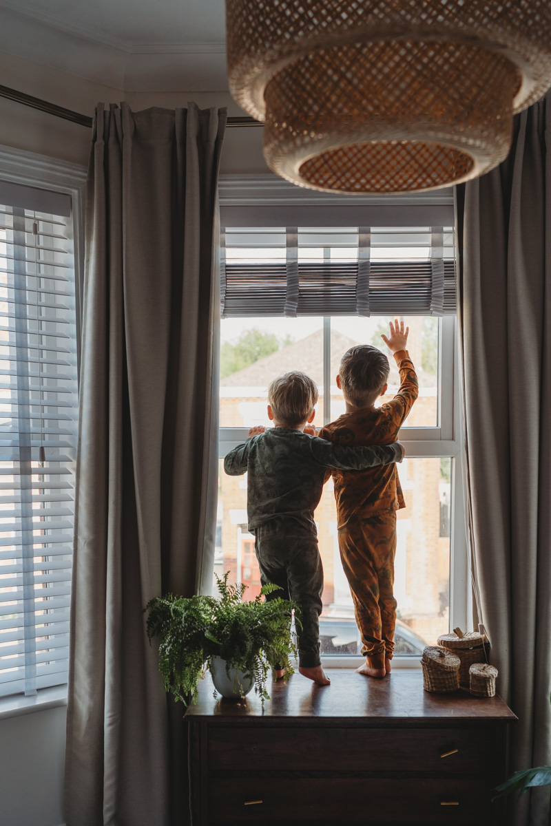two small boys staring out of the window in lockdown 2020