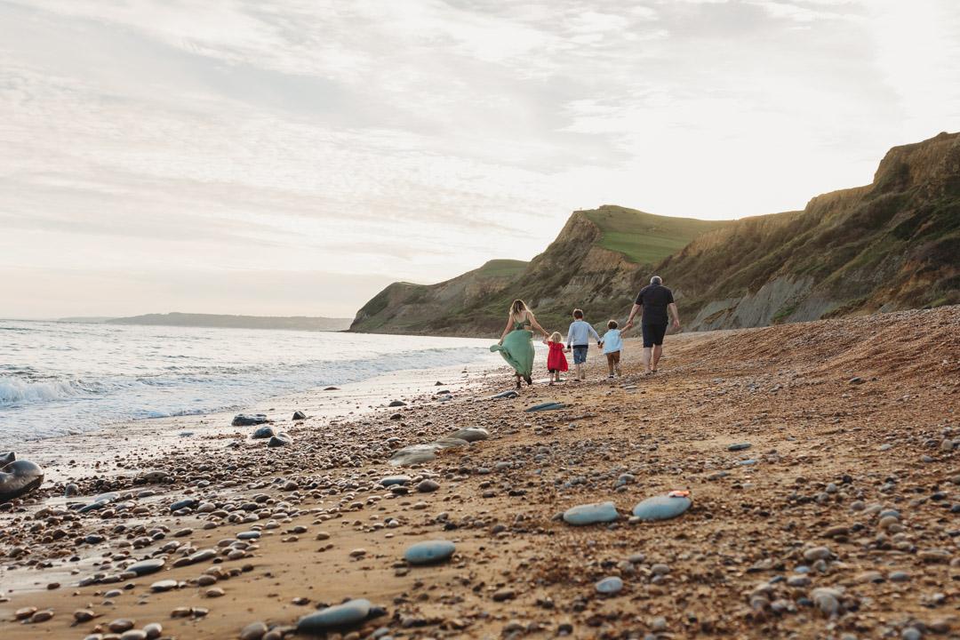 Family on Eype beach at sunset running towards the sea