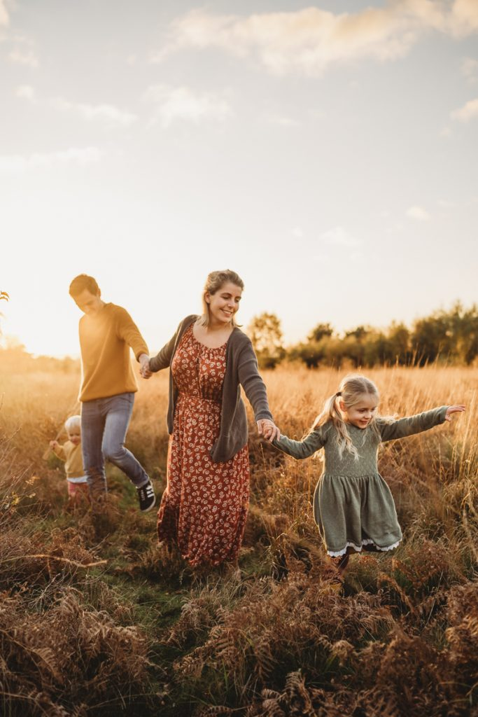 Family being lead through a field at sunset wearing beautiful clothes i long grass
