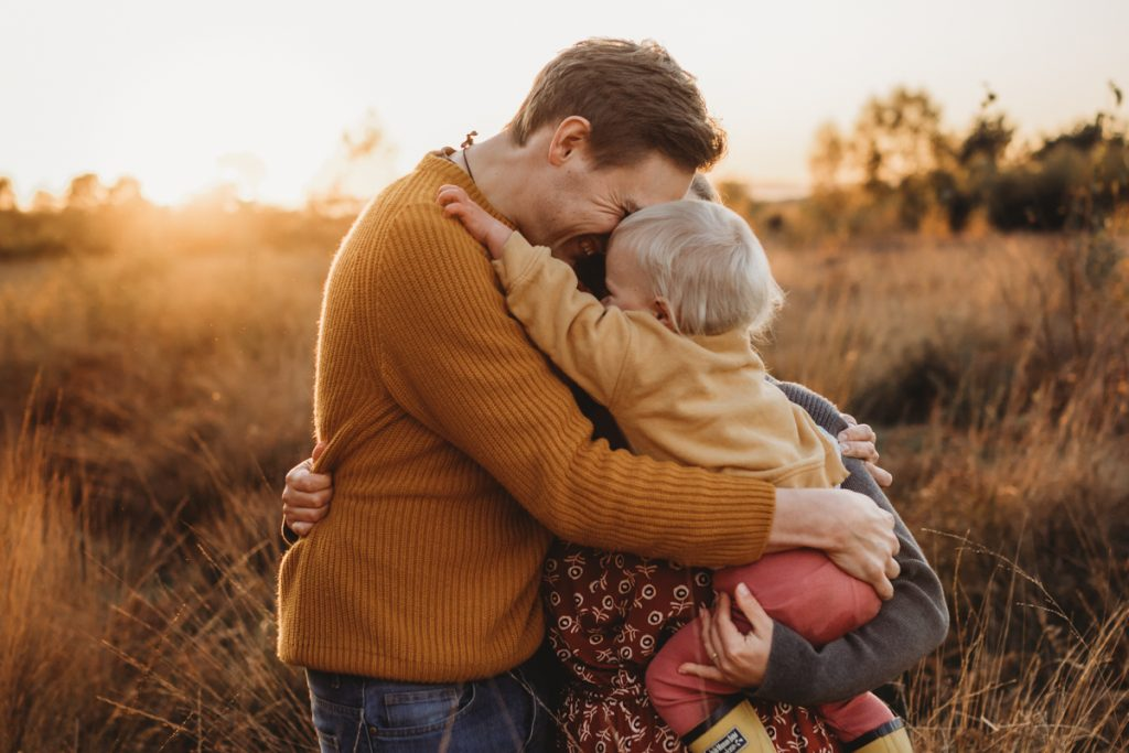 Dad and mum having a cuddle in the sunset and golden grass is during a Family Sunset Photo shoot