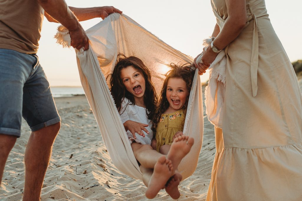 laughing girls being swung in the blanket on the beach with their parents either side at sunset