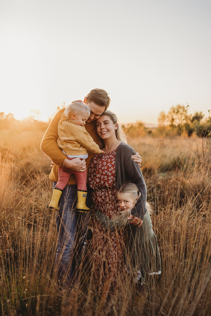 family cuddles at golden hour in a field