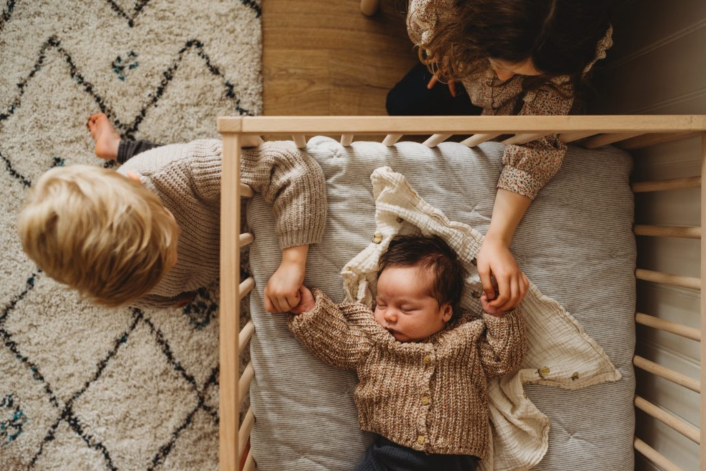 birds eye view of newborn baby in cot with brother and sister holding their hands through rails