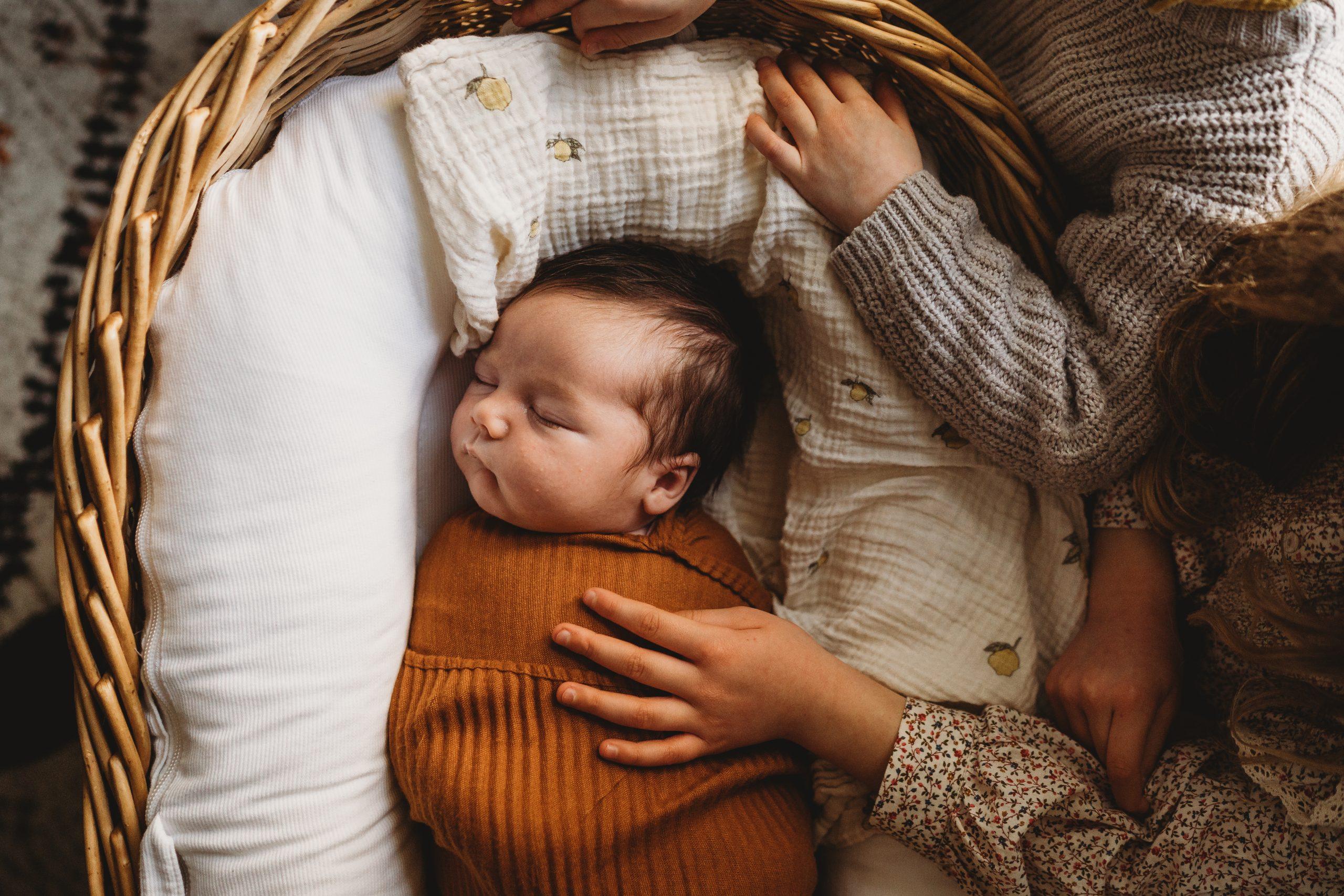 family cuddling on saiofa at home with newborn