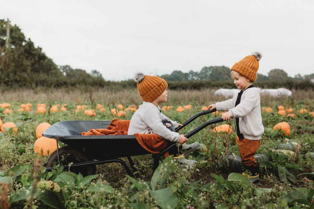 kids riding in a wheelbarrow on sunnyfields pumpkin farm