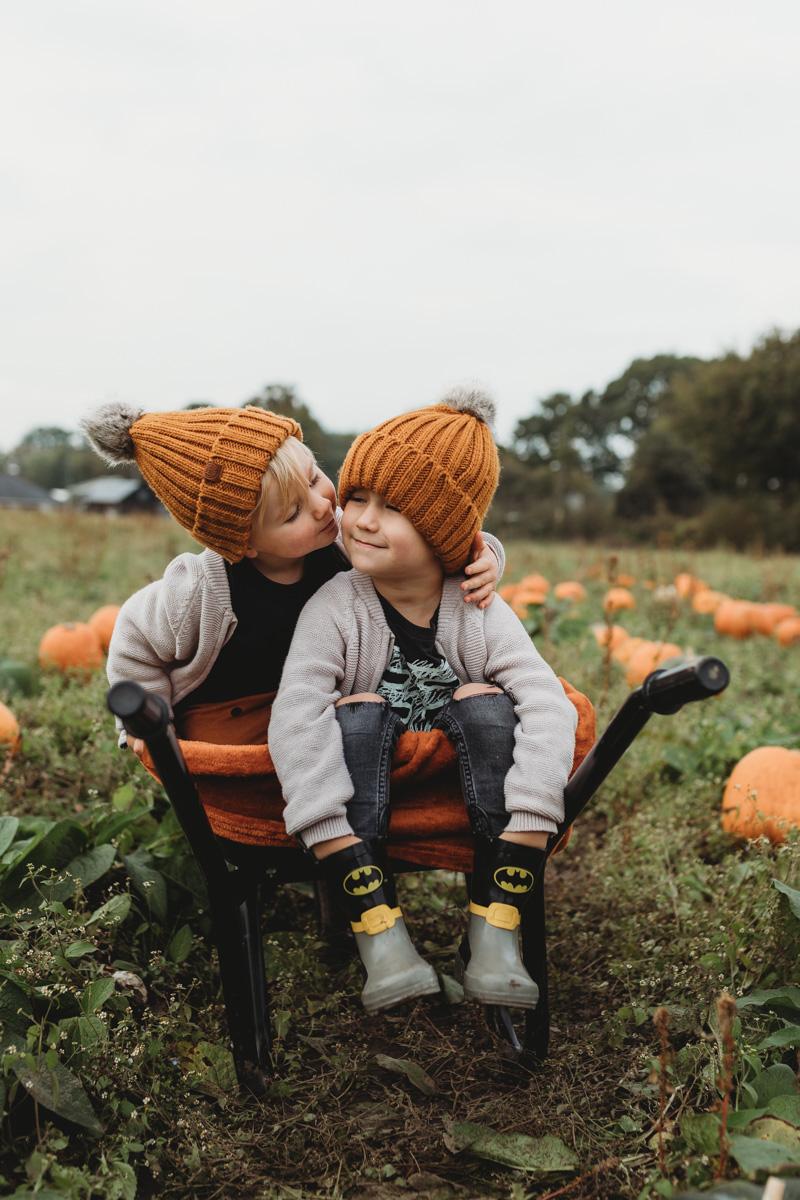 kids kissing in a wheelbarrow on sunnyfields pumpkin farm