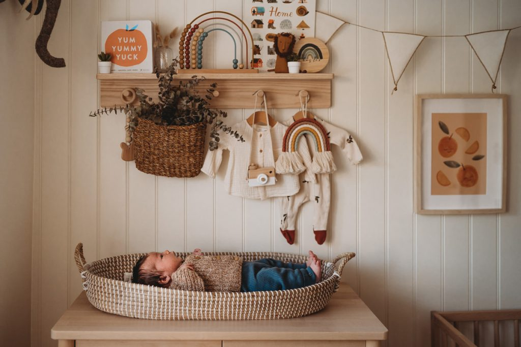 newborn baby laying on wicker changing mat was home