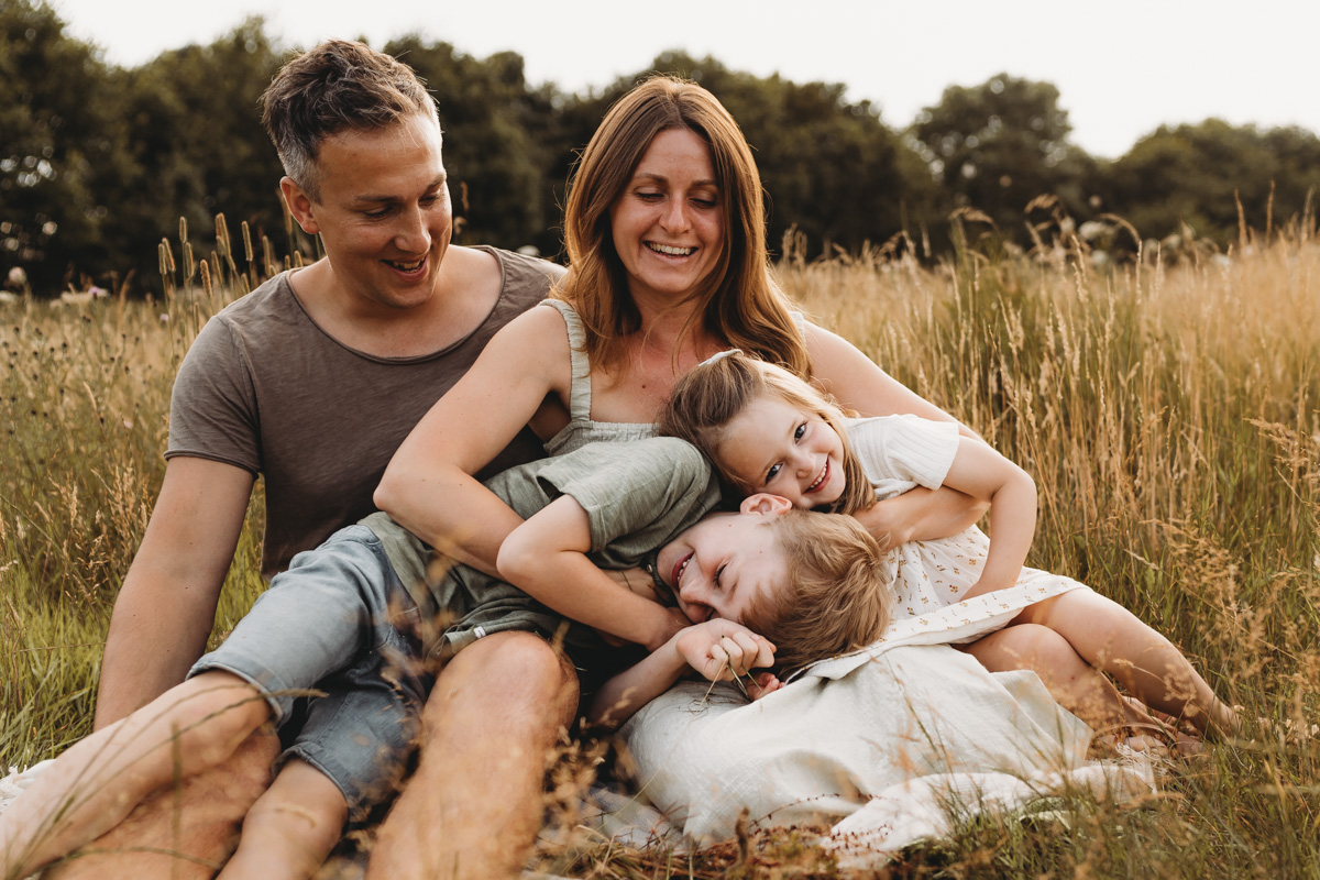A family bundled together in a field of long grass together at sunset looking relaxed