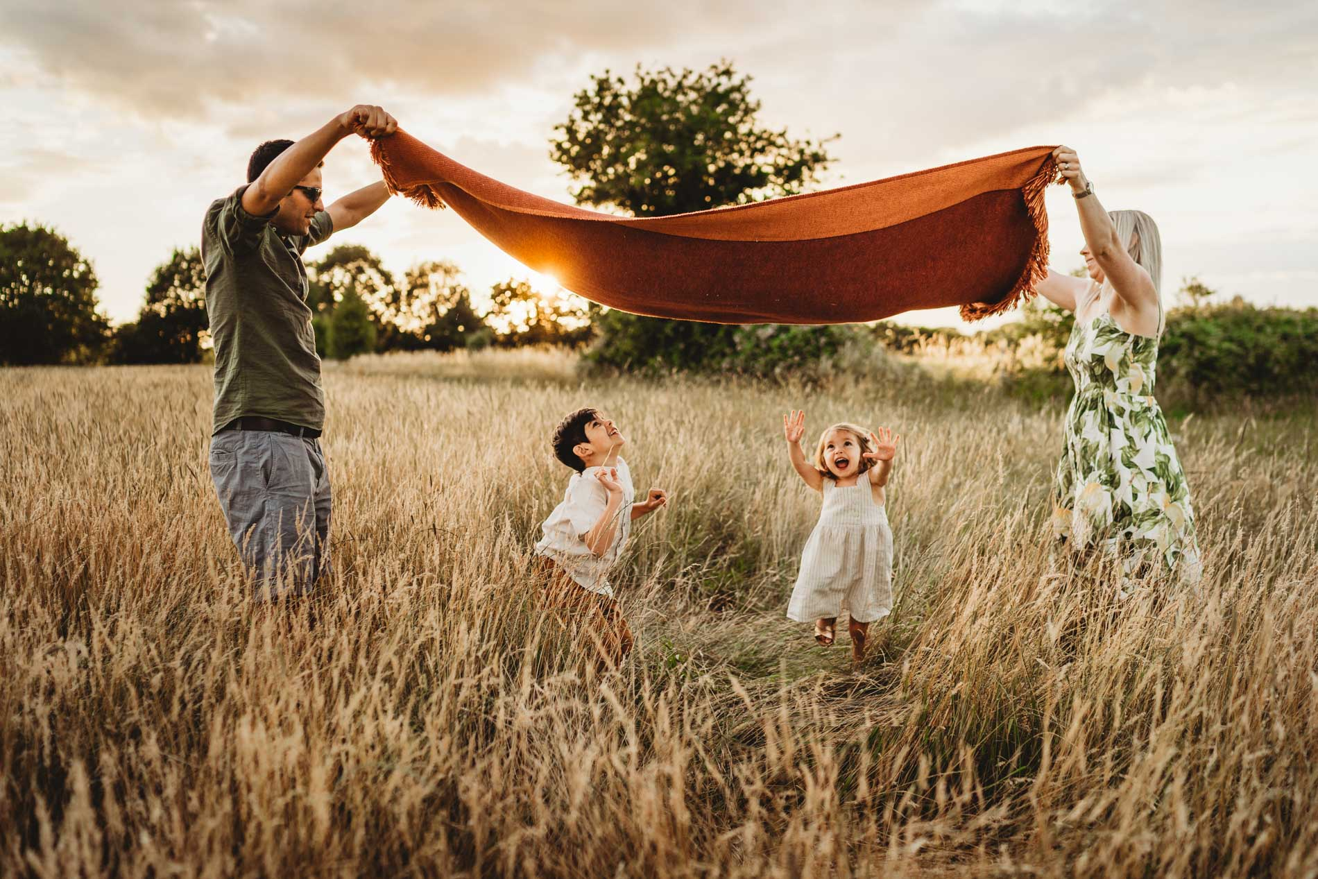 Picture of a family during a sunset photo shoot playing with an orange blanket whilst the children run underneath in the long summer grass