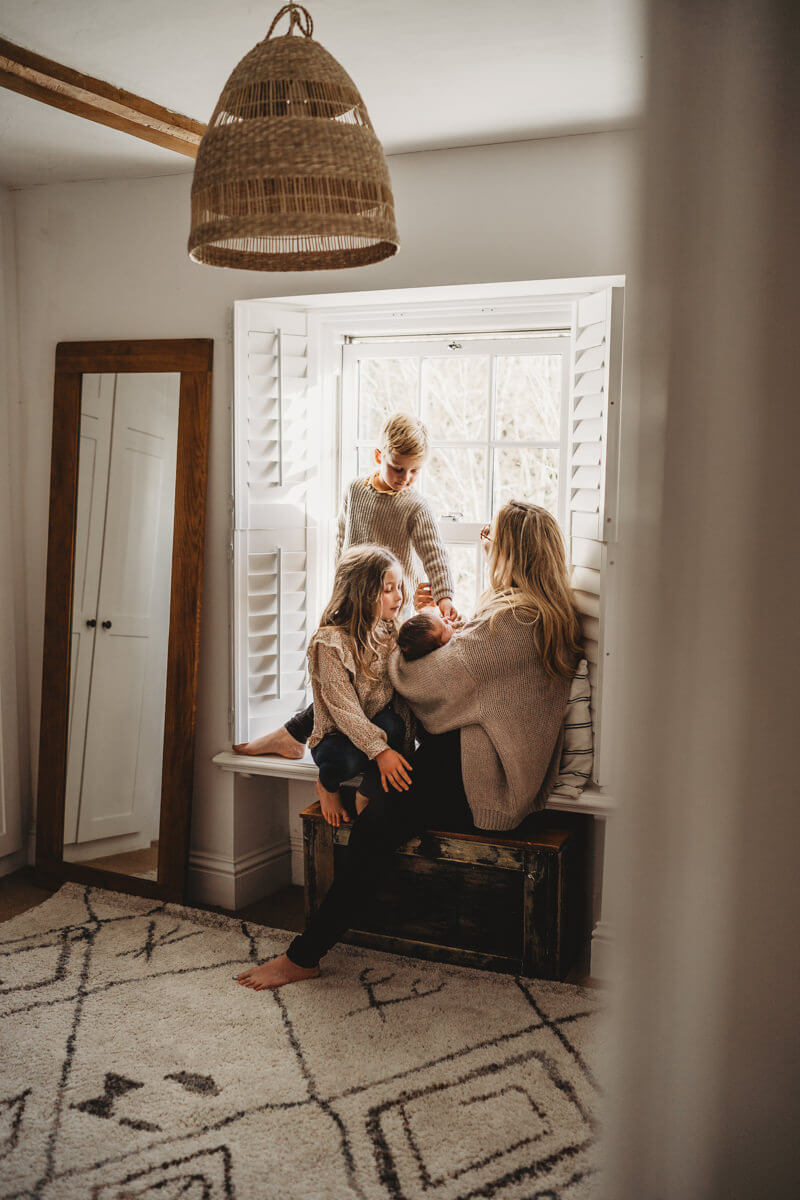 newborn baby with mum and siblings in window relaxed newborn photography hampshire